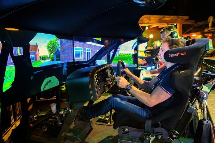 Hermen Kobus geconcentreerd en vol gas gevend  in actie op de simulator van Kevin Abbring. 'Dichterbij het echte werk kom je niet.'