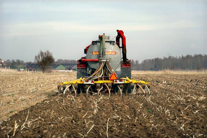 Een loonwerker rijdt met een tractor over het land om mest in de bodem te injecteren.
