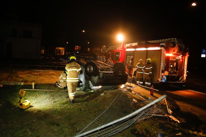 De auto vloog door een bouwhek over de kop.