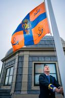 De huismeester van Paleis Huis ten Bosch hijst de Koninklijke standaard.