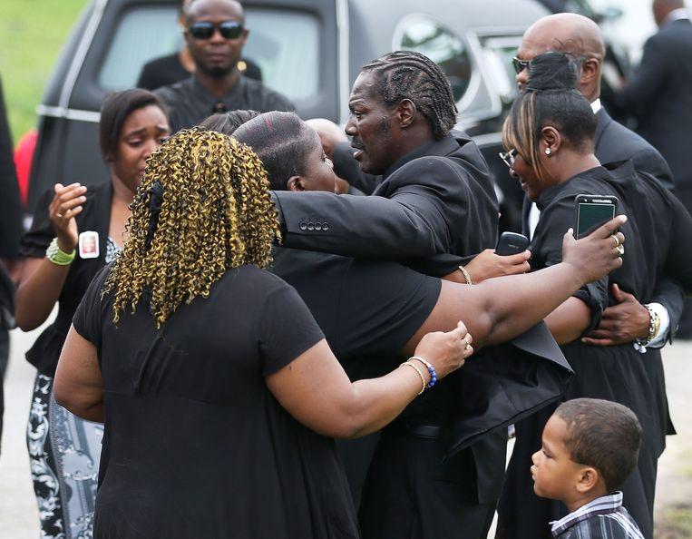 Gary Washington (centraal) wordt ondersteund bij de begrafenis van zijn moeder Ethel (70), één van de slachtoffers.