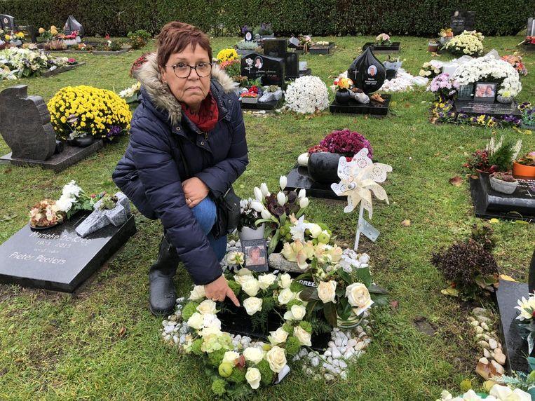 Christiane Liessens bij de mooi verzorgde grafsteen van haar dochter. In één jaar tijd werden er echter al vijf bloemstukken van gestolen.