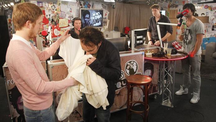 DJ Gerard Ekdom ruikt aan de jurk van Doutzen Kroes die acteur Robert de Hoog (links) ter veiling aanbiedt.