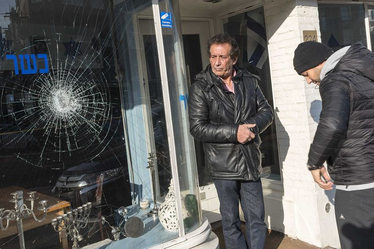 Eigenaar Daniel Baron (R) staat met zijn vader voor het Israëlische restaurant HaCarmel en laat de schade aan zijn restaurant zien, 2 maart.  Beeld ANP