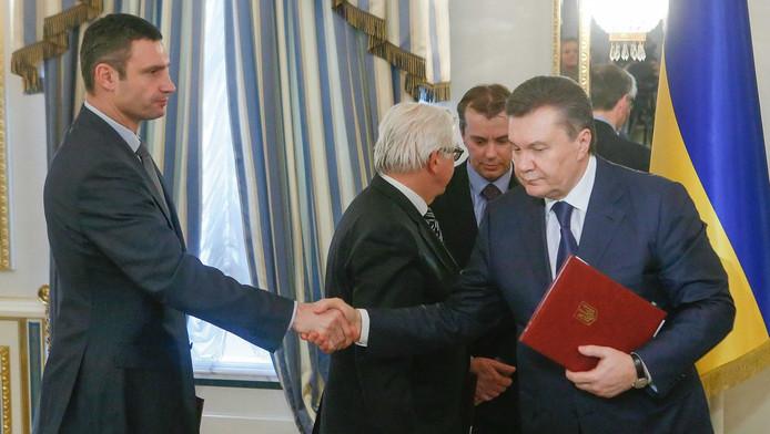 De voormalige president van Oekraine Viktor Janoekovitsj (R) schudt de hand van oppositieleider Vitali Klitsjko