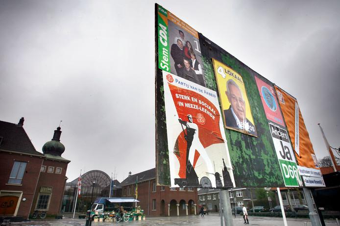 Veel raadsleden in kleinere gemeenten zijn tegen een fusie met een buurgemeente. Maar vaak is hun eigen gemeente ook al ooit ontstaan door een fusie. Op de foto: verkiezingsbord in Heeze-Leende. Op de achtergrond het gemeentehuis.