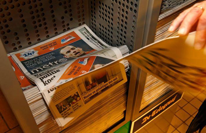 Een krantenbak met daarin de Metro op Amsterdam CS