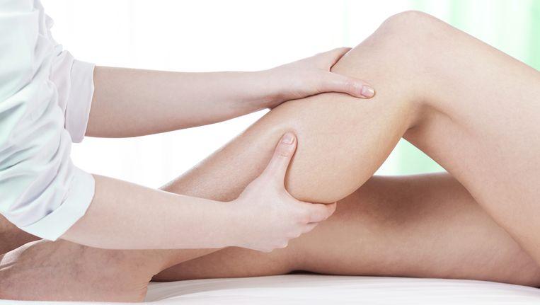 Een fysiotherapeut bezig met het linkerbeen van een patiënt. Beeld Thinkstock