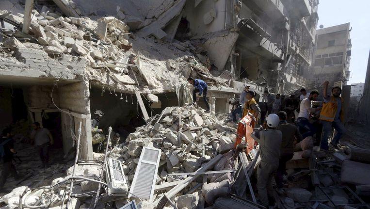 Bewoners zoeken naar overlevenden na een bomaanslag in Aleppo die onder andere een school heeft geraakt. Beeld Reuters