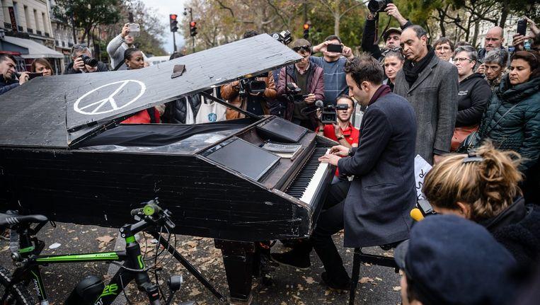 Pianist Davide Martello speelt na de aanslagen Imagine, voor het Parijse theater Bataclan. Beeld epa