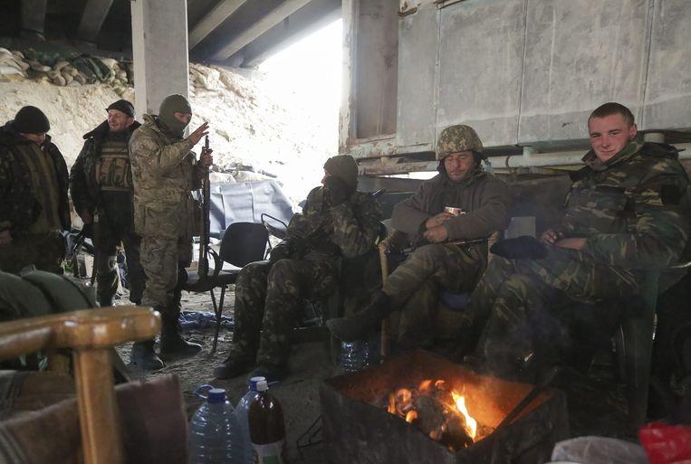 Oekraïense soldaten nemen een pauze bij hun post vlakbij de luchthaven van Donetsk. Beeld epa