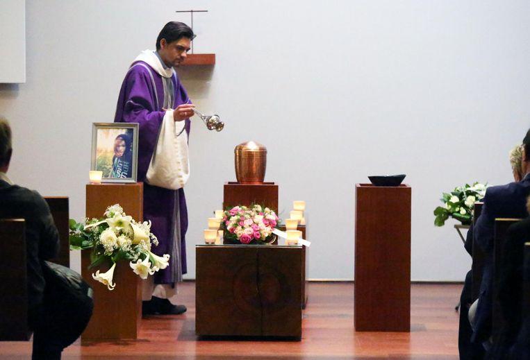 De priester zegent de urne van Jeson.