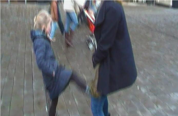 Still uit het genoemde filmpje. Een meisje 'schopt' een AH-medewerker zachtjes tussen de benen. Het personeel van de supermarkt wil niet herkenbaar in beeld.