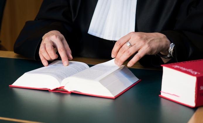 Foto ter illustratie: Een rechter met wetboek in de rechtszaal.