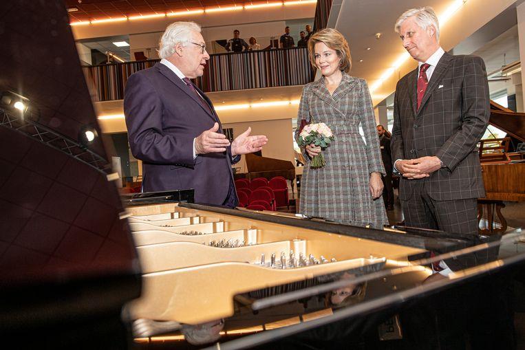 Eigenaar Chris Maene geeft het vorstenpaar een woordje uitleg over de unieke gepatenteerde rechtsnarige piano van het bedrijf.
