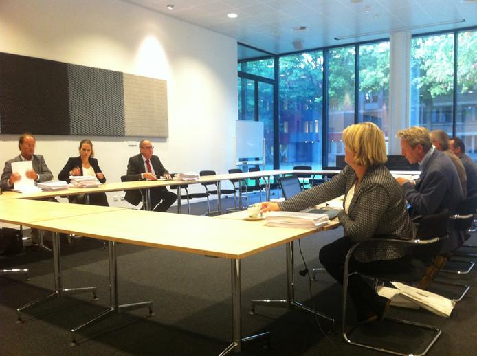 Drie Osse ambtenaren en bedrijfsadviseur Ton Gobits (met stropdas) zitten tegenover de bezwaarschriftencommissie van de gemeente Oss.