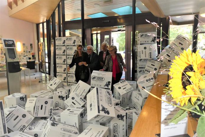 Archieffoto: v.l.n.r. Rita van de Wouw (Bint), Martin Hol (bibliotheek Brenthof), Henk van Hemmen (De Huif) en wethouder Lianne van der Aa duwen verhuisdozen weg bij de ingang van het gemeentehuis in Sint-Michielsgestel.