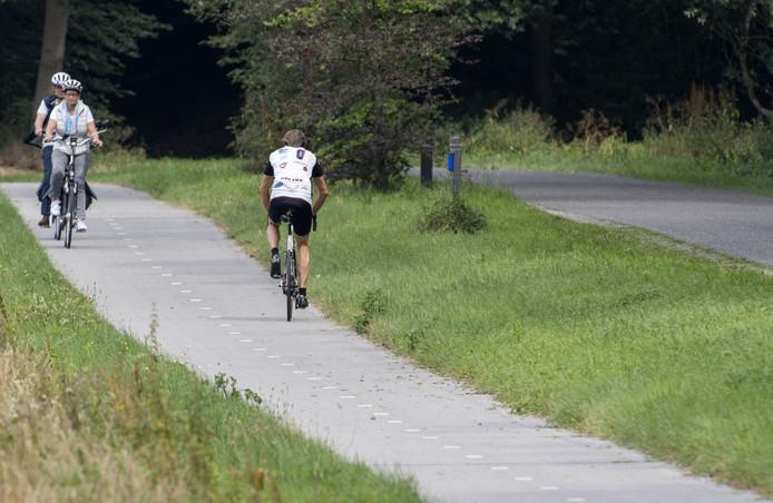 Een toerfietser rijdt op het fietspad naast de Hooidijk tegen de Vasser Bult op. In de afdaling gaan wielrenners vaak de hoofdrijbaan op.