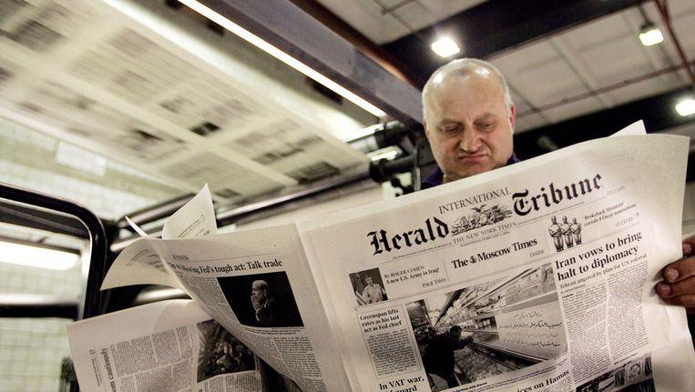 Een werknemer van een drukkerij bekijkt een International Herald Tribune in Moskou in 2006. Beeld AFP