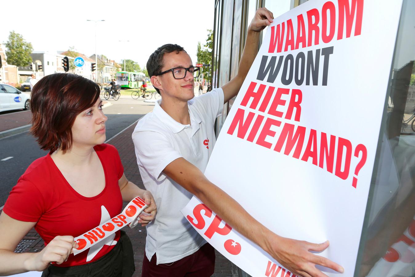 Tim van Elswijk samen met Iris van der Kolk in actie. Ze plakten posters tegen leegstand op de ruiten van een pand bij het Alphense station.