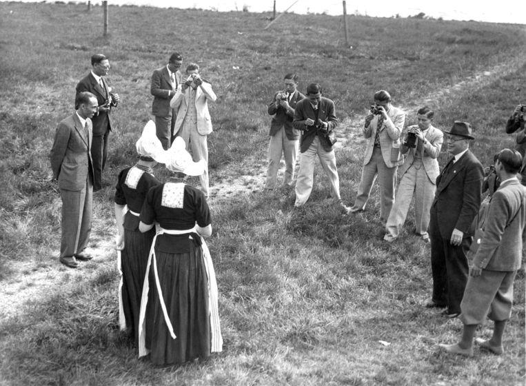 Vrouwen in klederdracht op de foto gezet tijdens trip naar Volendam van Chinees Olympisch voetbalelftal dat tegen Ajax zal spelen. Volendam, 1936. Beeld Hollandse Hoogte / Spaarnestad P
