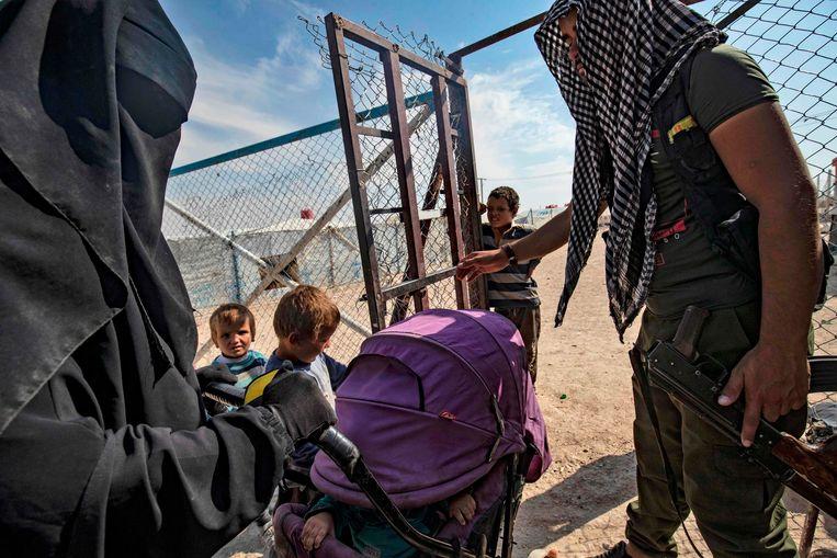 Een bewaker met IS-vrouwen en -kinderen in het kamp Al-Hol in Syrië. Beeld AFP