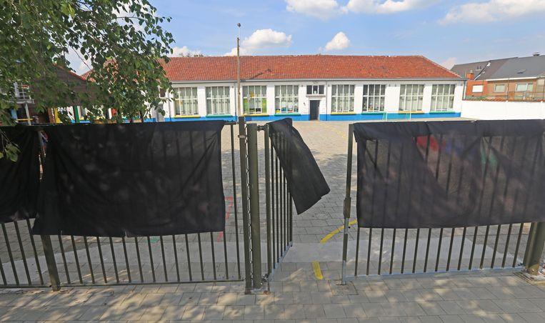 De schoolpoort werd bedekt met zwarte doeken, als protest tegen de overname.