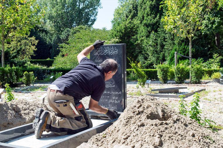 Werknemer Ismail van de firma Natuursteen plaatst een islamitische grafzerk op begraafplaats Crooswijk in Rotterdam.  Beeld  Hans van Rhoon