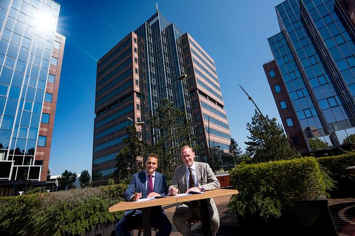 Wethouder Frank van Liempdt (links) en de projectontwikkelaar Jonald Bouwhuis zetten hun handtekening. De drie kantoortorens aan de Planetenbaan op de achtergrond worden verbouwd tot appartementencomplex.