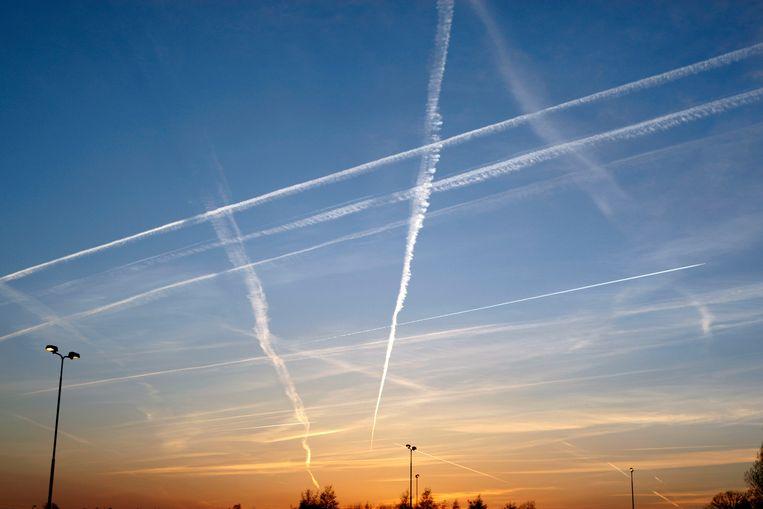 Strepen in de lucht van een vliegtuig bij ondergaande zon. Beeld ANP