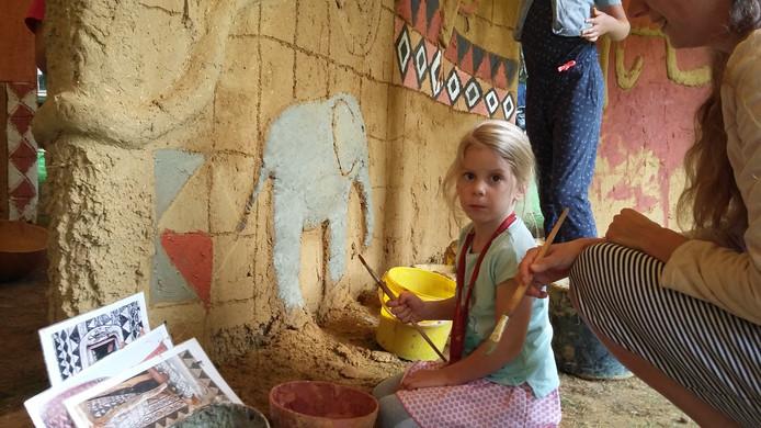 Sophia Pater (4) beschildert een olifant op de lemen muur.