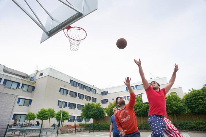 Vluchtelingen basketballen op het speelveldje voor de noodopvang in Oss.