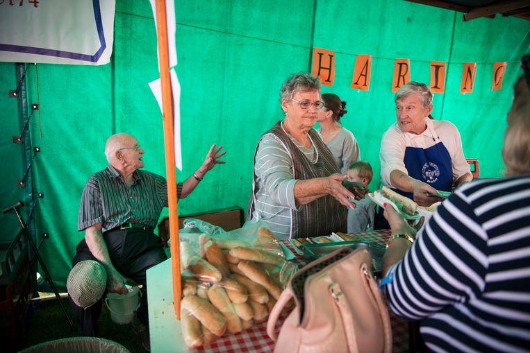 Nora de Rijk-Van der Laan (rechts) verkoopt haring op de Oranjemarkt. Haar man Jan de Rijk (links) zit naast de koelbox met vis. Beeld Bram Lammers