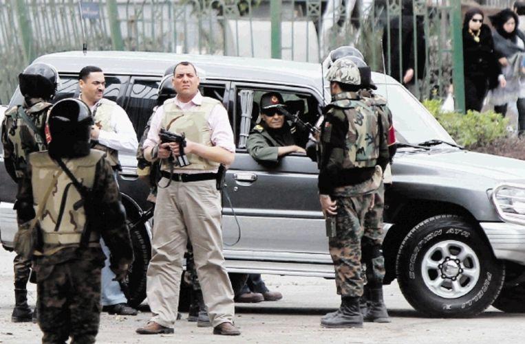 Bodyguards houden de wacht als minister van defensie Tantawi (inde auto) op 6 februari het Tahrirplein bezoekt. (FOTO AFP) Beeld AFP