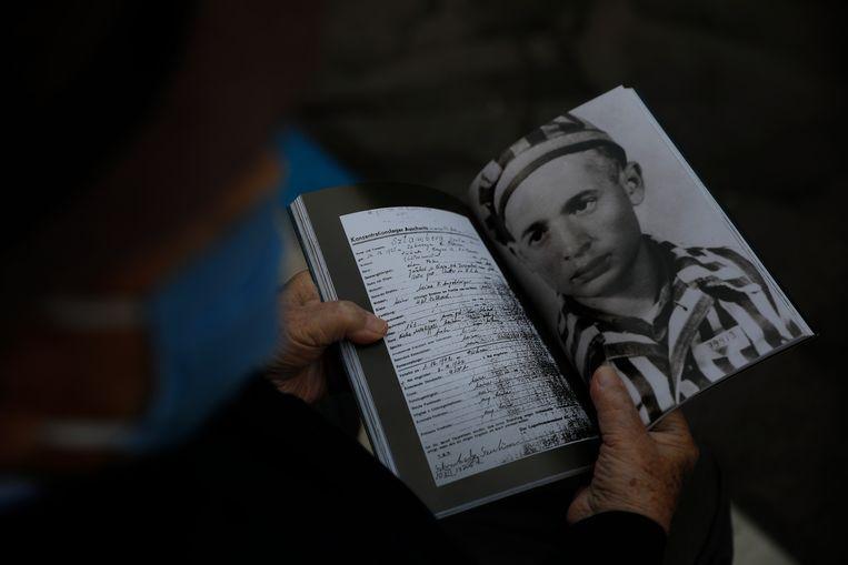 Holocaust-overlever Shalom Stamberg houdt een boek vast met een foto van hemzelf in  Auschwitz. Beeld AP