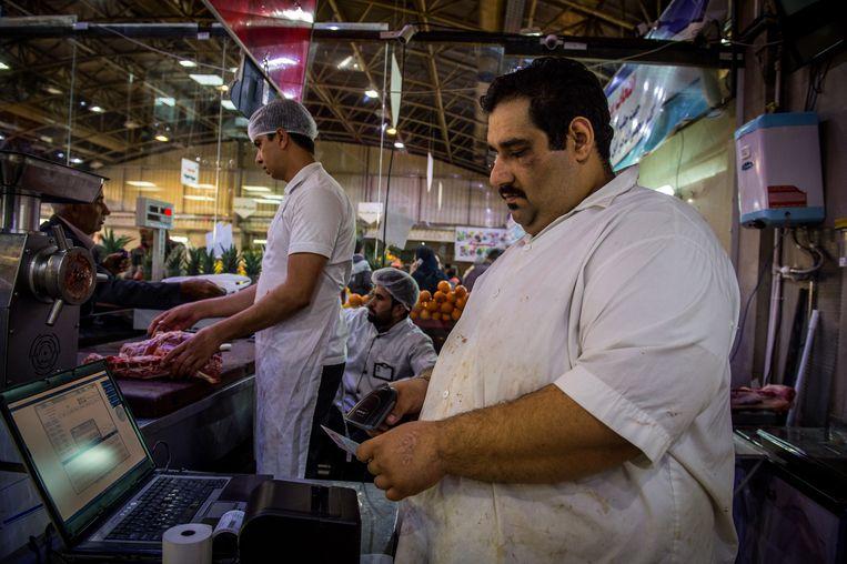 Een slager scant in Teheran een identiteitsbewijs van een klant die vlees koopt in een staatswinkel. Beeld  Getty Images
