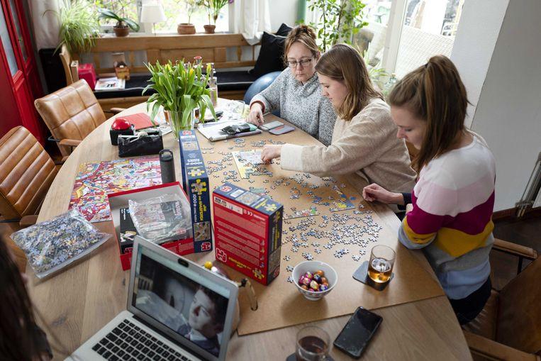 Een gezin puzzelt aan de eettafel om de tijd te verdrijven. Beeld ANP