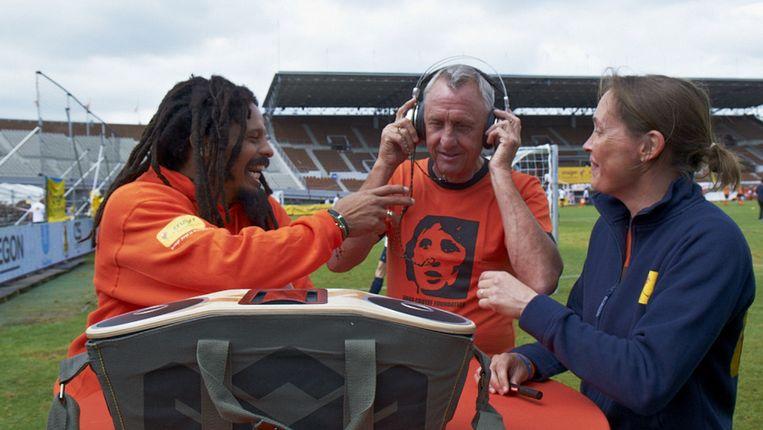 Johan Cruijff (m) in actie voor de Johan Cruyff Foundation. Links de zoon van Bob Marley, Rohan. Beeld