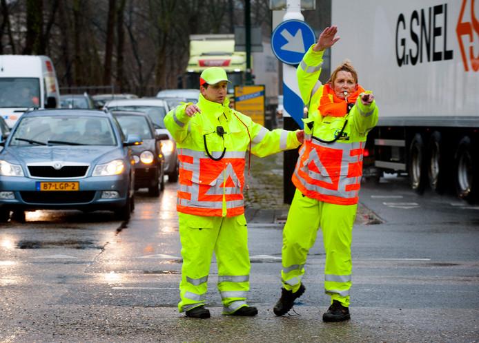 Verkeersregelaars (hier op een andere kruising in Woerden) lijden het verkeer vanwege De Nacht van Woerden in goede banen op de kruising van de Stationsweg met de Oudelandseweg en Utrechtsestraatweg.