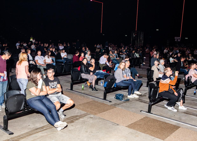 Plukjes mensen op setjes van drie aan elkaar bevestigde stoelen. Beeld Hilde Harshagen