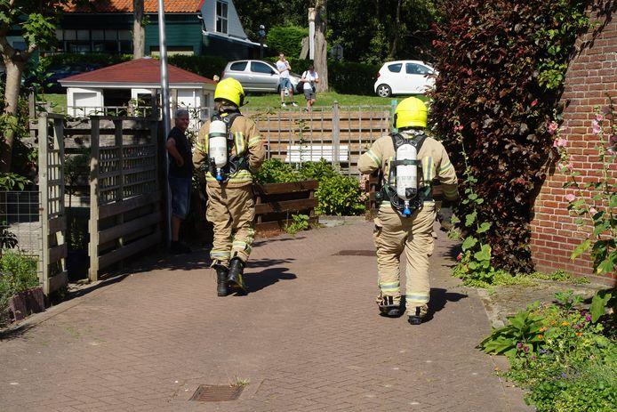 De brandweerlieden gaan lopend naar het schuurtje waar brand was uitgebroken