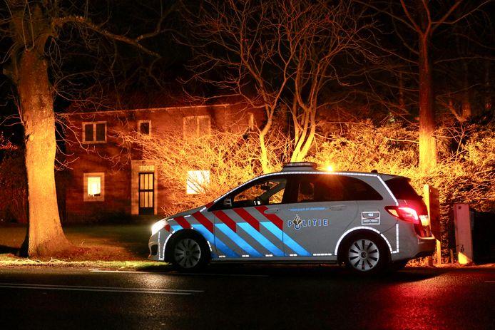 Een politiewagen bij de woning waar de overval plaatsvond.