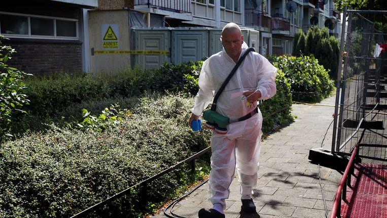 Een medewerker van asbestsaneringsbedrijf Oskam haalt waardevolle papieren voor bewoners uit de met asbest besmette woningen in de wijk Kanaleneiland, op 30 juli.. Beeld ANP