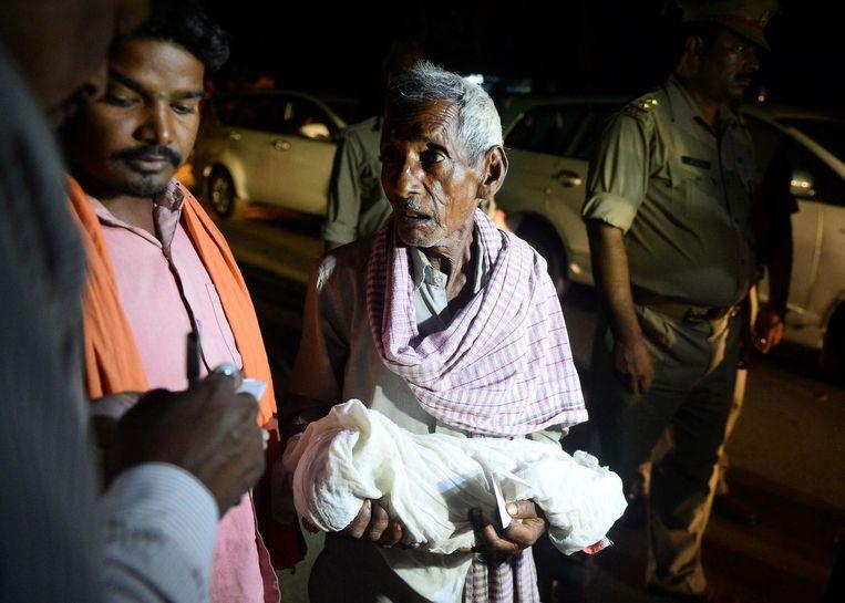 Een nabestaande draagt een overleden kind het ziekenhuis uit. Beeld afp