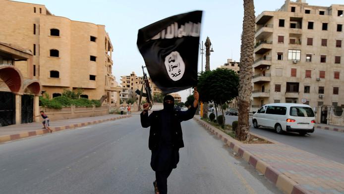 Een lid van ISIS (Islamitische Staat in Irak en groot-Syrië) zwaait met de vlag van ISIS in Raqqa.