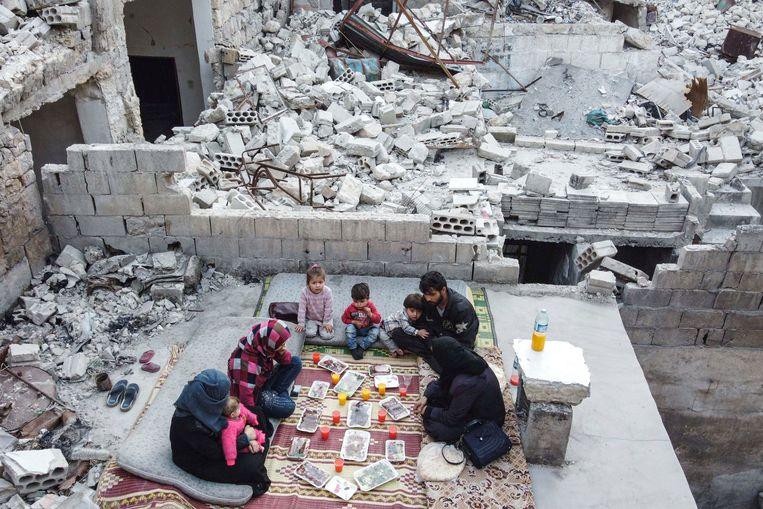 In de Noordwest-Syrische provincie Idlib eet een familie de iftar-maaltijd in wat nog over is van hun huis. Beeld AFP
