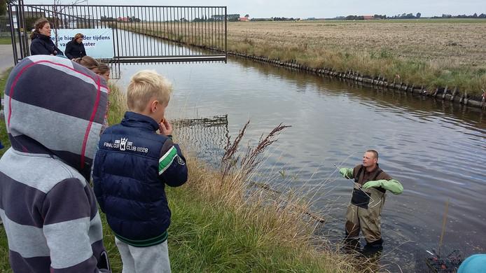 Rattenvanger Kees Kristalijn in actie, de kinderen kijken toe.
