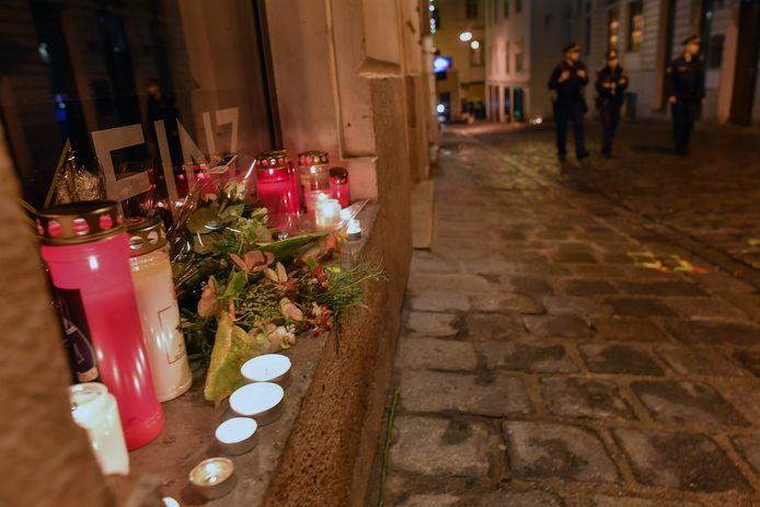 Een politiepatrouille wandelt voorbij kaarsjes en bloemen op de plek waar iemand het leven liet tijdens de terreuraanslag in Wenen.