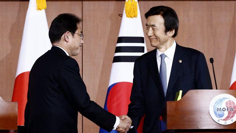 De Japanese minister van Buitenlandse Zaken Fumio Kishida (links) en zijn Zuid-Koreaanse collega Yun Byung-Se (rechts) schudden maandag handen na een persconferentie in Seoul. Beeld EPA