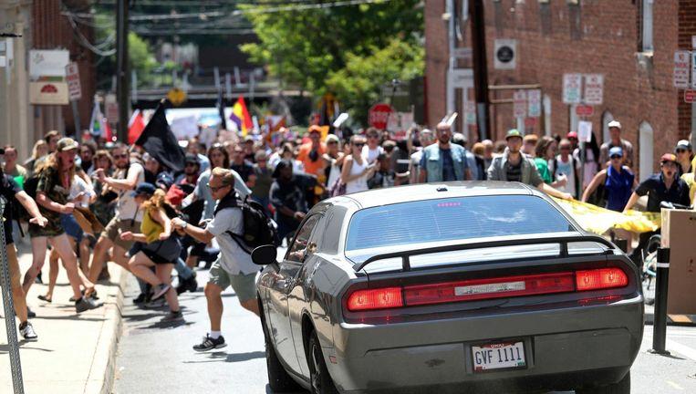 De auto rijdt op hoge snelheid in op de demonstranten, waarop hij achteruit de straat weer uit spoedt. Beeld ap